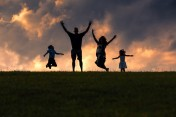Silhouette of jumping family with amazing sky