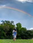 brothers looking up at rainbow