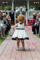 Little curly redhead flower girl throwing petals