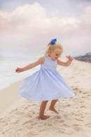 little girl in blue dress twirling on beach
