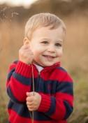 Little boy holding tall blade of grass