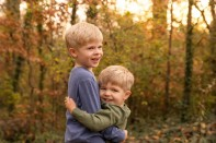 Boys hugging in front of fall foliage