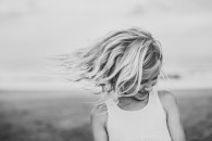 young girl with hair blowing in wind on beach