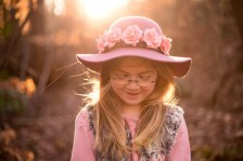 Child wearing pink hat at sunset