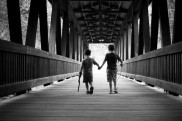 brothers holding hands on covered bridge