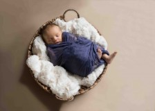 baby in basket asleep by window light