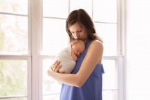 mom holding and kissing swaddled newborn
