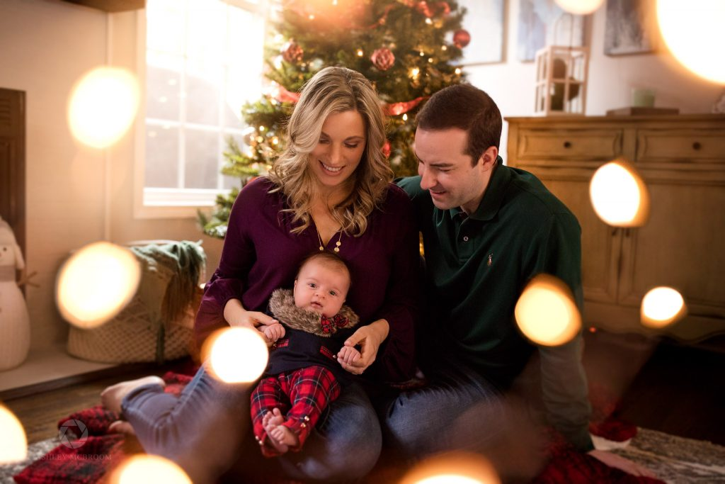 Parents and their baby in front of holiday tree with christmas lights on