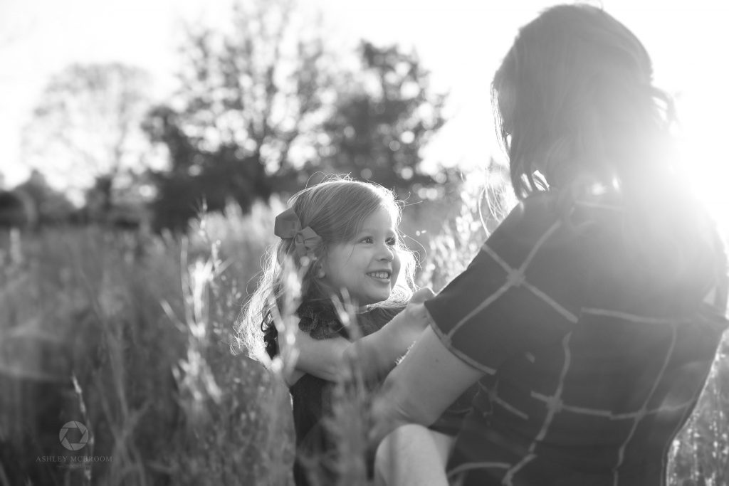 Mom holding daughter in field roswell photographer