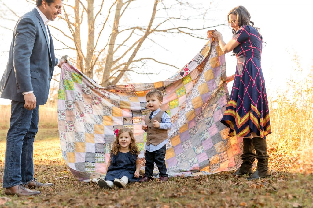 Parents holding grandmothers quilt with children