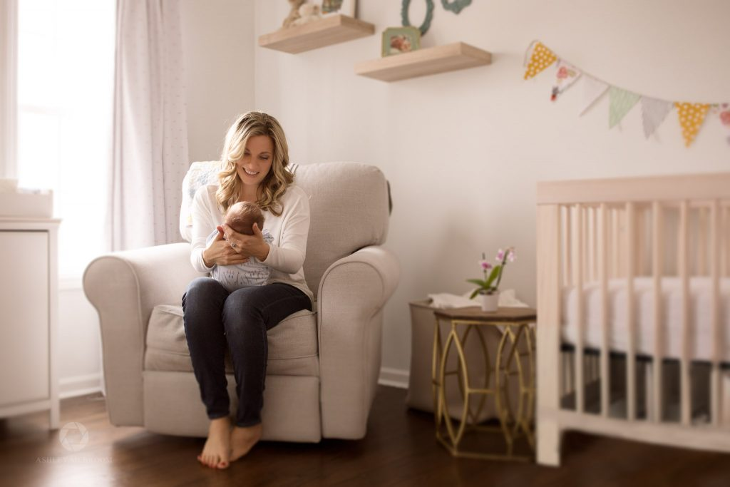 Mom with holding baby in rocker in nursery