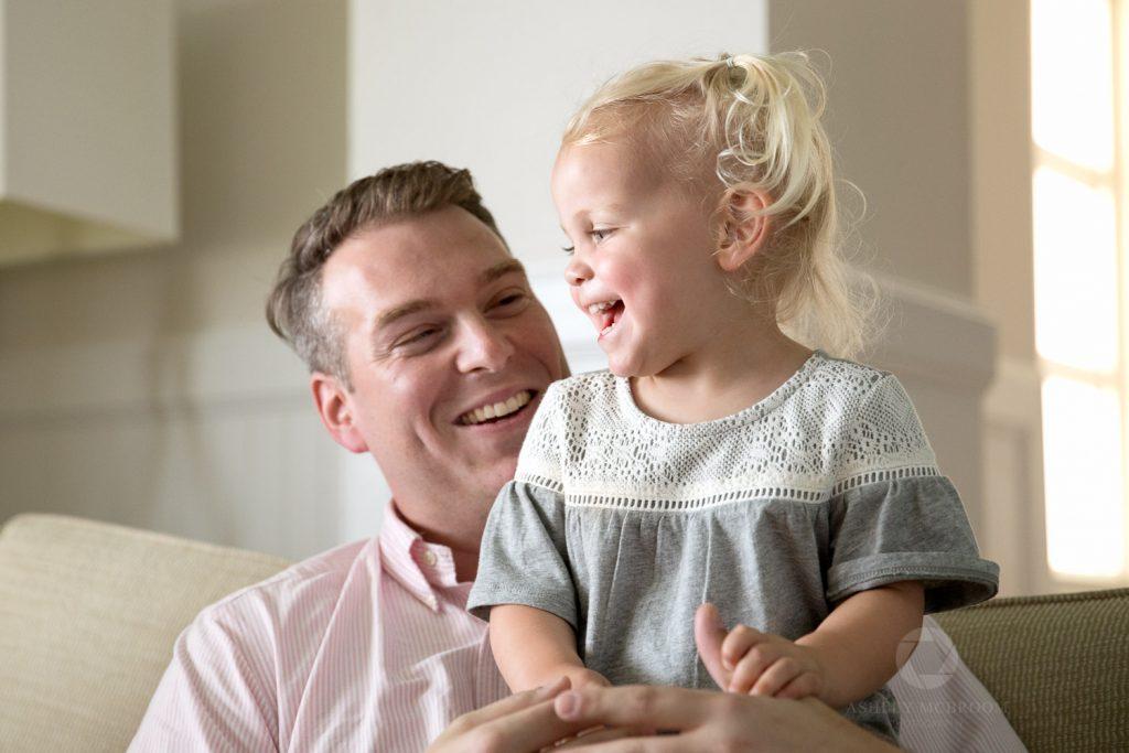 Dad smiling at cute daughter