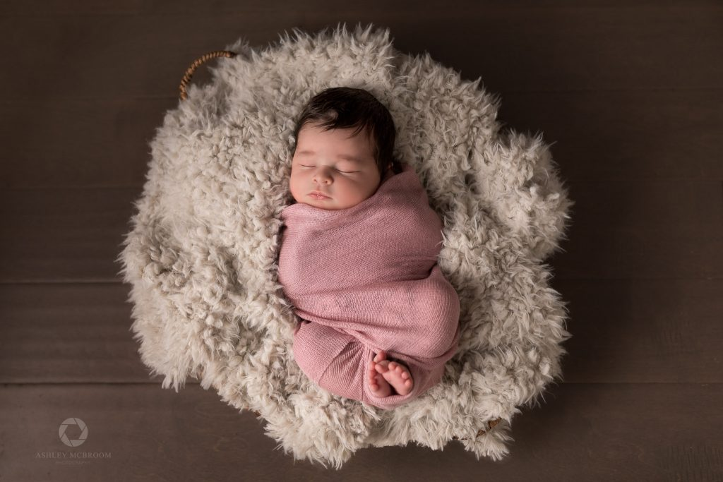 baby in basket with pink swaddle and toes out