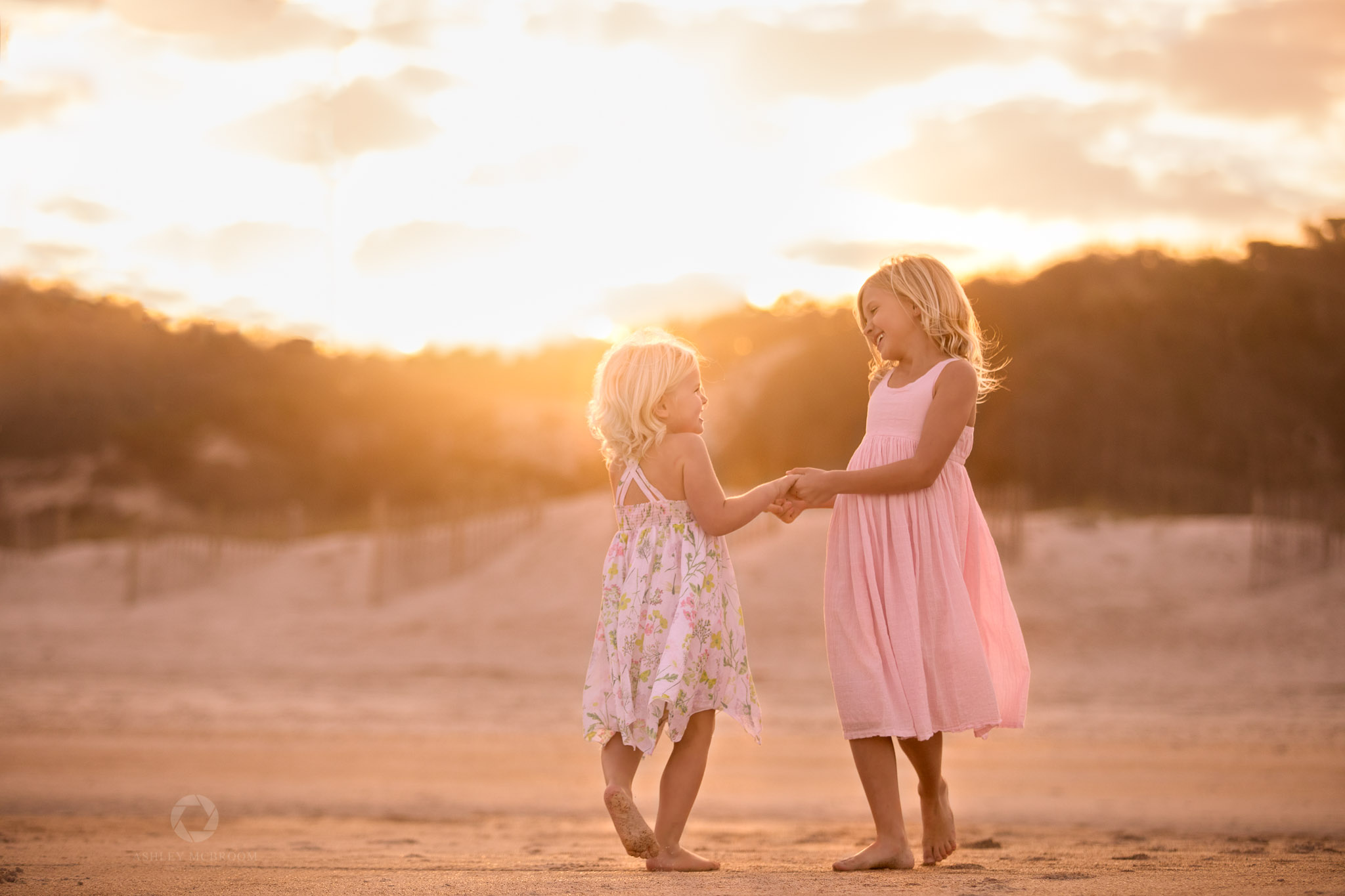 beautiful sisters holding hands in sunlight
