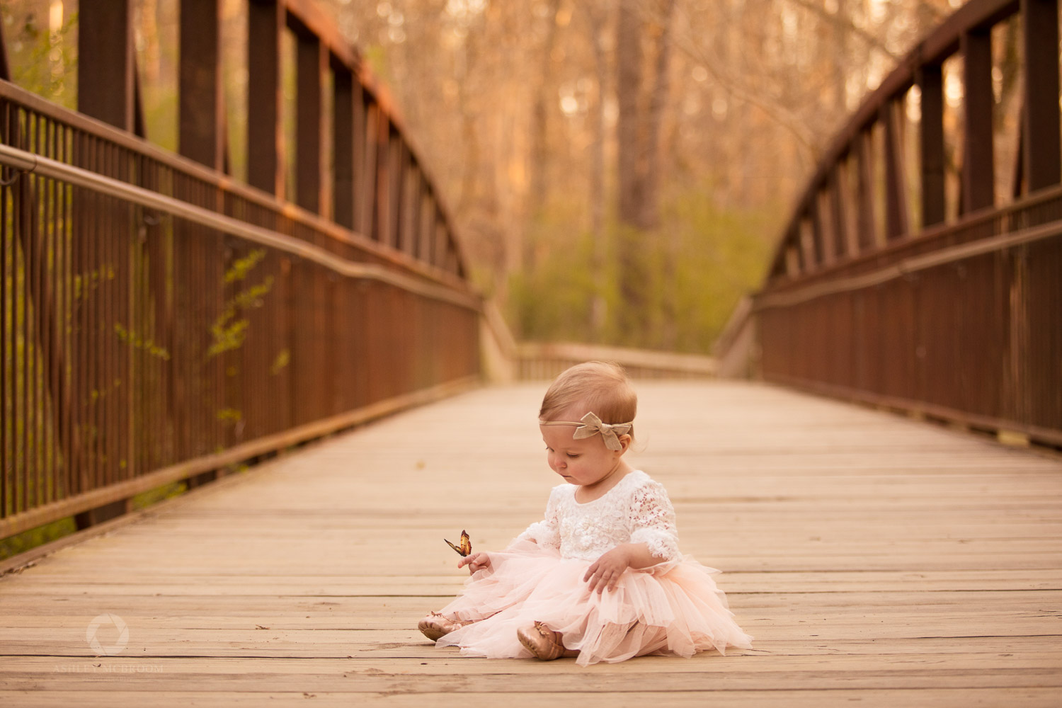 One year old girl on bridge with butterfly