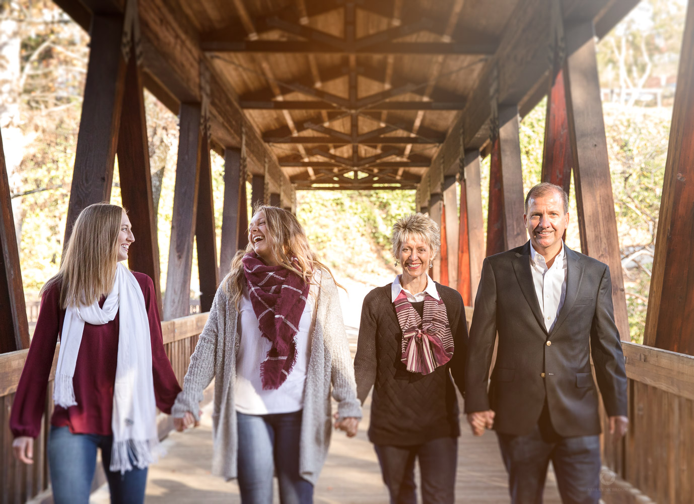 Roswell family photographer holding hands on covered bridge