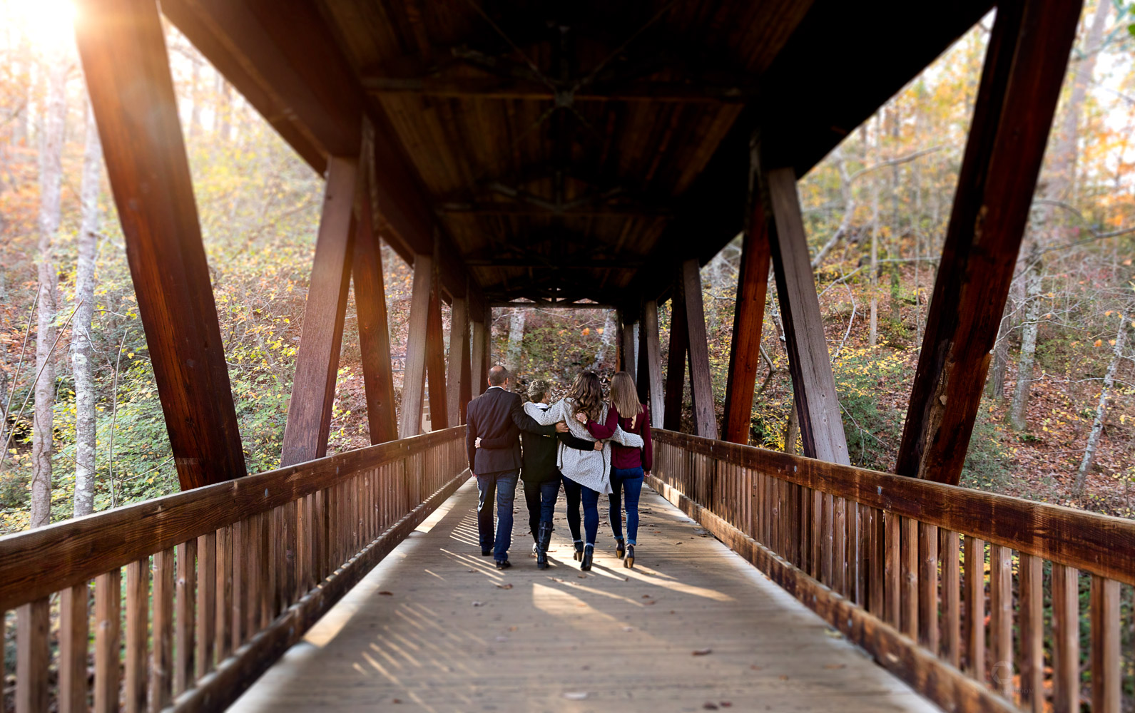 Family Walking on covered bridge Roswell mill