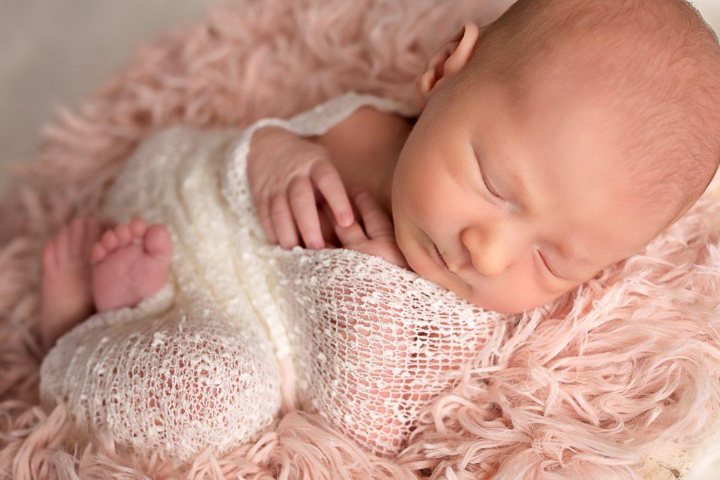 Newborn girl in cream wrap