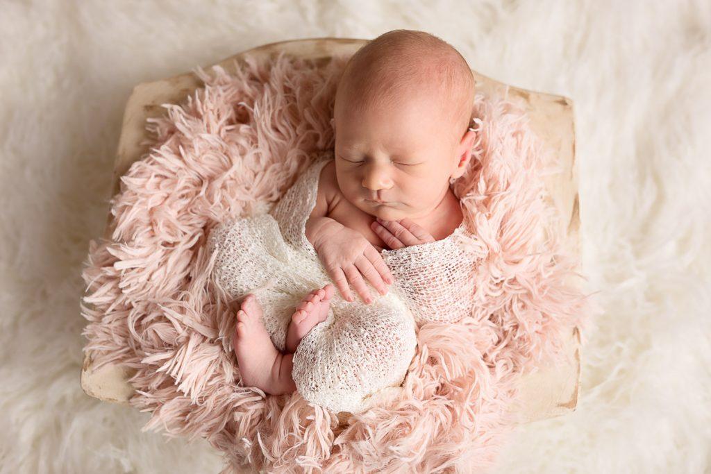 newborn girl in wooden bowl