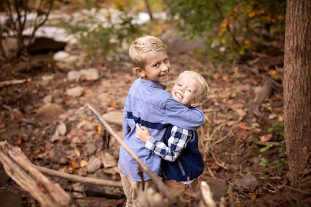 happy brothers in the woods giving a hug