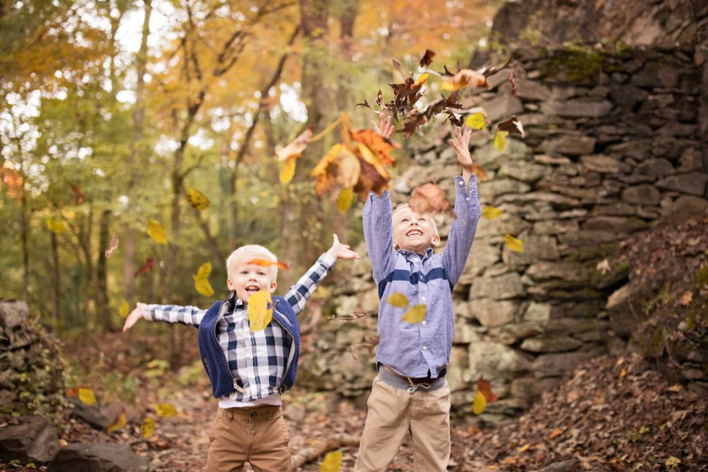 boys throwing leaves in the air during their photo session