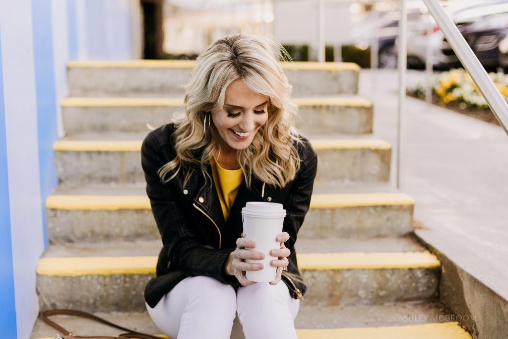 girl laughing with cup of coffee during photo shoot