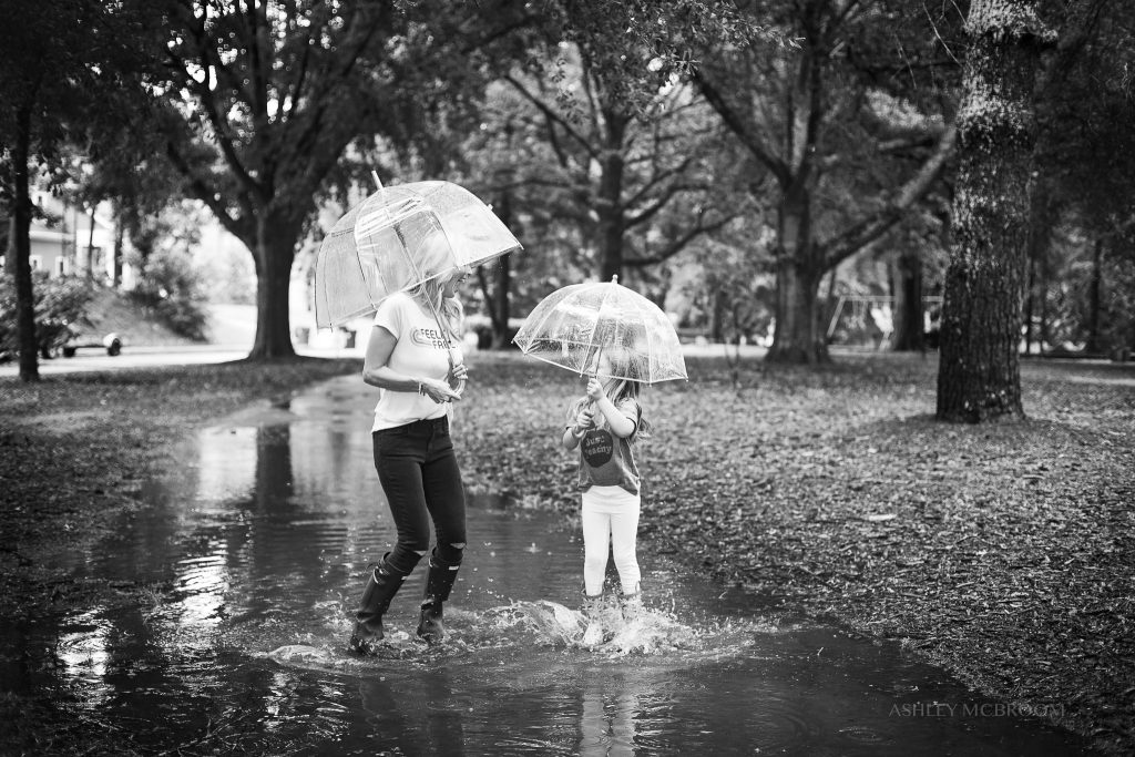 mom and daughter jumping in the rain