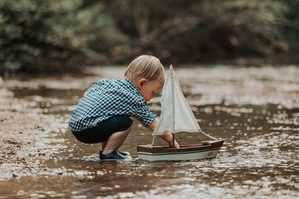 little boy in creek with sailboat family pics marietta